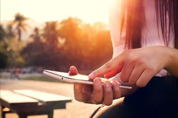 Close up of a woman using mobile smartphone in sunset image small
