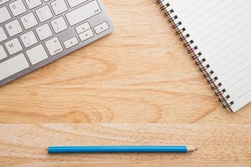 Office table with keyboard, pencil and notebook image small