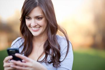 A portrait of a woman texting with her phone image small